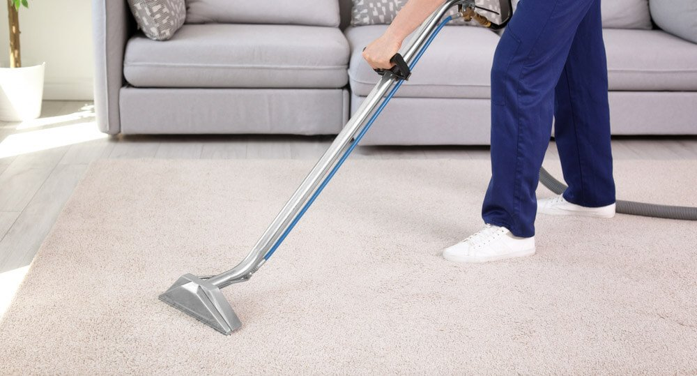 Carpet cleaning technician using carpet cleaning machine